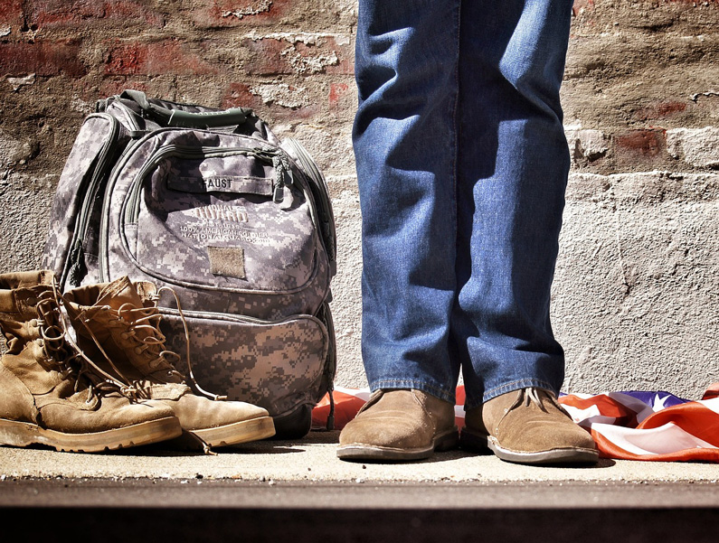 image showing hiking boots and tactical backpack on the floor