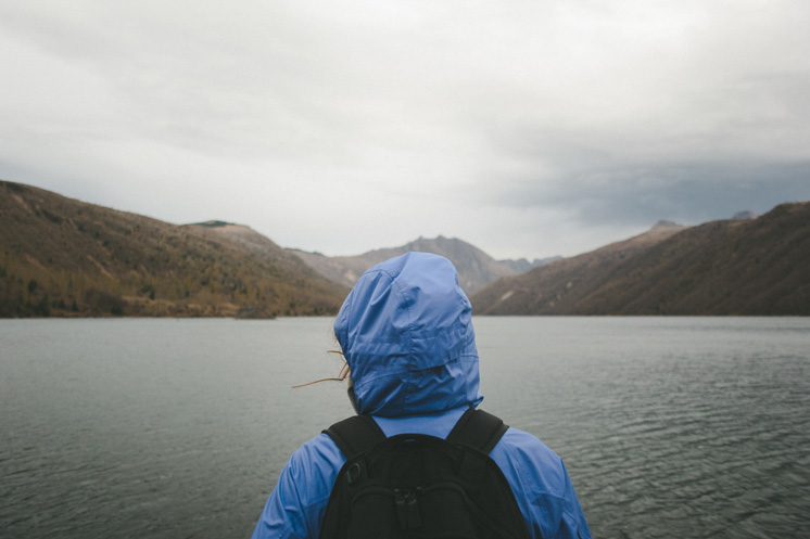 person standing in front of a lake and wearing waterproof gear